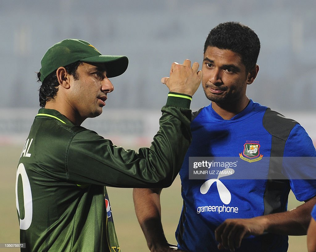 Pakistani cricketer Saeed Ajmal (L) shows bowling tips to Bangladehis cricketer Mohammad Mahmudullah during the third one day international cricket match between Bangladesh and Pakistan at the Zahur Ahmed Chowdhury Stadium in Chittagong on December 6, 2011. Pakistan won by 58 runs. AFP PHOTO/Munir uz ZAMAN