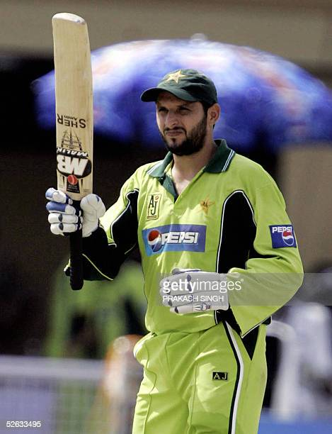 Pakistani cricketer Shahid Afridi acknowledges the crowds applause after scoring a century during the fifth one day international cricket match...