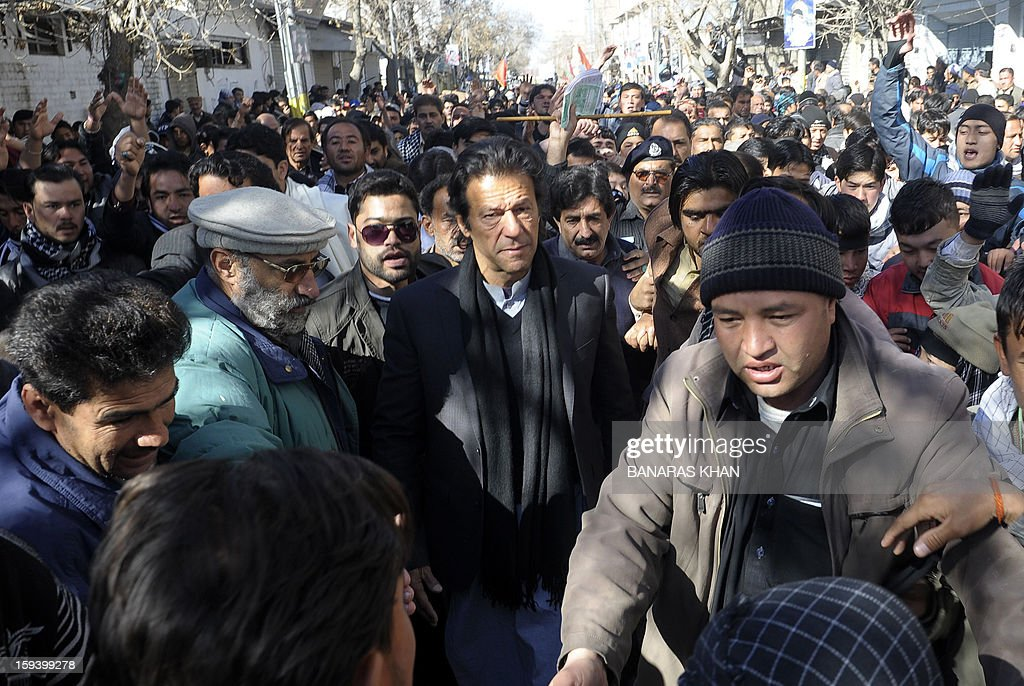 Pakistani cricketer turned politician Imran Khan (C) walks as he arrives to meet demonstrators of Shiite Muslim families who refusing to bury their dead in Quetta on January 13, 2013, on the third day of protest. Pakistan's Prime Minister Raja Pervez Ashraf arrived in the southwestern city of Quetta to meet Shiite Muslim families refusing to bury their dead after devastating bombings. AFP PHOTO/ Banaras KHAN