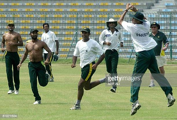 Pakistani cricketer Younis Khan is watched by newly appointed team coach Bob Woolmer as he jumps in the air while preparing to throw a ball to his...