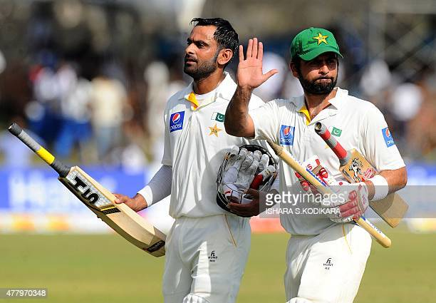 Pakistani cricketers Ahmed Shehzad and Mohammad Hafeez leave the field after winning the opening Test match between Sri Lanka and Pakistan at the...