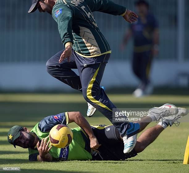 Pakistani cricketers Ahmed Shehzad and Sarfraz Ahmed play football during a practice session at the Sharjah cricket stadium in Sharjah on December 10...
