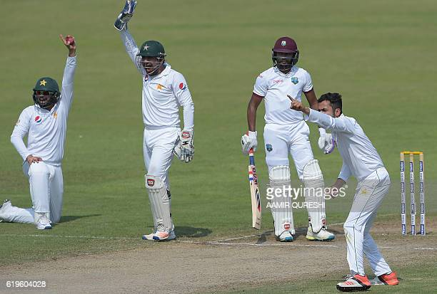 Pakistani cricketers Azhar Ali Sarfraz Ahmed and Mohammad Nawaz appeal for catch against West Indies' batsman Devendra Bishoo on the third day of the...