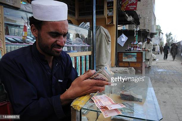 A Pakistani currency dealer counts Afghan currency at the border between Pakistan and Afghanistan at Torkham on May 20 2012 There was no sign of...