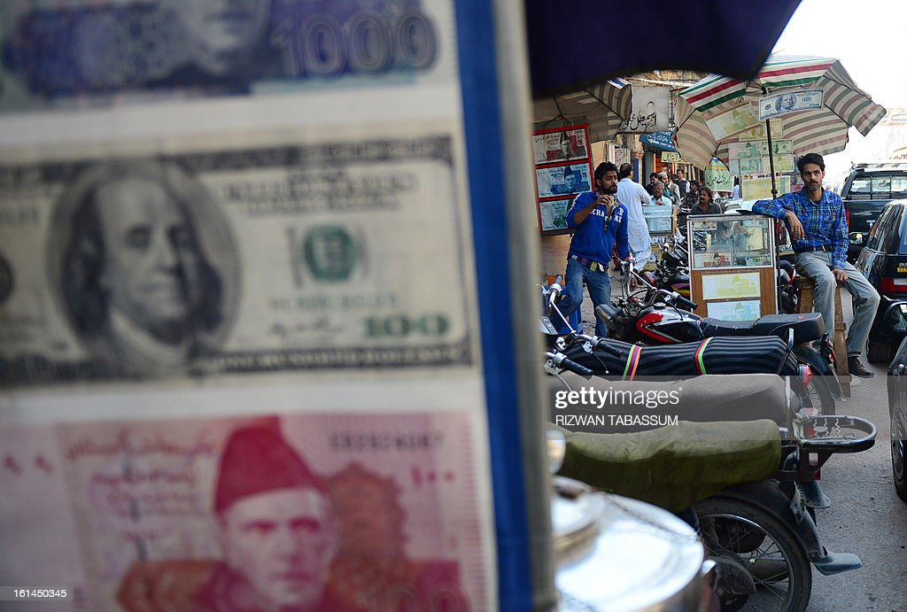Pakistani currency dealers wait for customers at a roadside currency exchange stall in Karachi on February 11, 2013. The Pakistani rupee on February 11 sank to an all-time low against the US dollar over forex reserve fears as the country repayed $146 million to the International Monetary Fund. AFP PHOTO/Rizwan TABASSUM