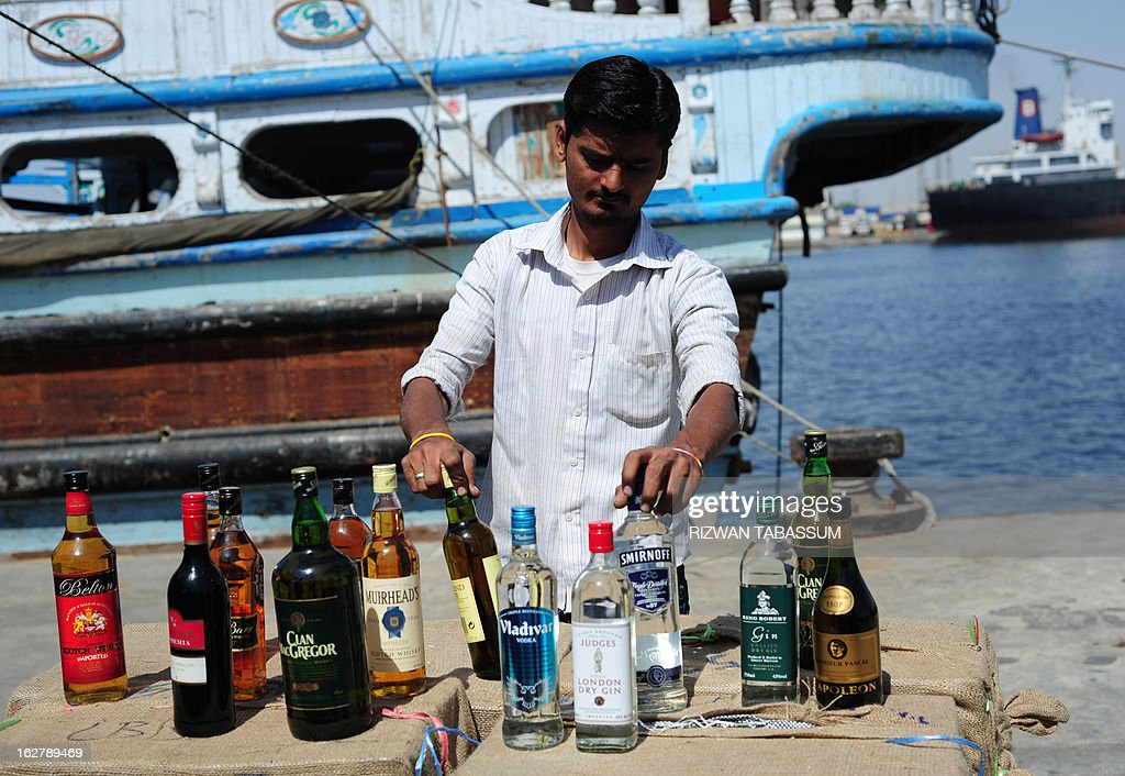 A Pakistani custom official arranges liquor bottles seized from smugglers in the Arabian Sea, in Karachi on February 27, 2013. Pakistan customs and Maritime Security Agency arrested 11 alleged smugglers, seized three boats along with 25,000 liquor bottles, 77,000 tins of beer and 55,000 litres of Iranian diesel in different operations they carried out while patrolling the Arabian Sea, according to maritime officials at a media briefing. AFP PHOTO/Rizwan TABASSUM
