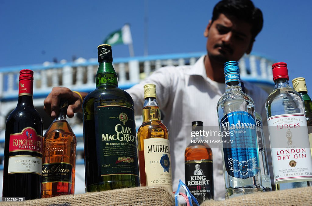 A Pakistani custom official arranges liquor bottles seized from the smugglers in the Arabian Sea, in Karachi on February 27, 2013. Pakistan customs and Maritime Security Agency arrested 11 alleged smugglers, seized three boats along with 25,000 liquor bottles, 77,000 tins of beer and 55,000 litres of Iranian diesel in different operations they carried out while patrolling the Arabian Sea, according to maritime officials at a media briefing. AFP PHOTO/Rizwan TABASSUM