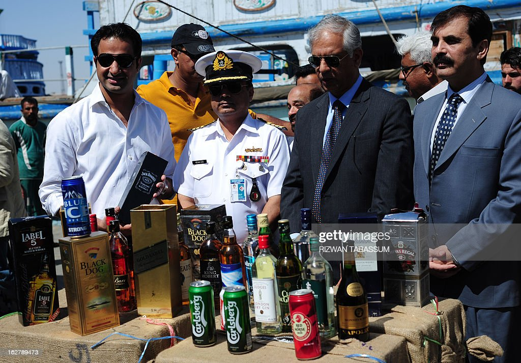 Pakistani custom officials poss for photographs infront of liquor bottles seized from smugglers in the Arabian Sea, in Karachi on February 27, 2013. Pakistan customs and Maritime Security Agency arrested 11 alleged smugglers, seized three boats along with 25,000 liquor bottles, 77,000 tins of beer and 55,000 litres of Iranian diesel in different operations they carried out while patrolling the Arabian Sea, according to maritime officials at a media briefing. AFP PHOTO/Rizwan TABASSUM