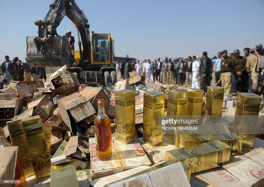 Pakistani custom officials prepare to destroy bottles of seized liquor at a ceremony in Karachi on January 26, 2014. Pakistani custom officials destroyed narcotics and other contraband items from different parts of the country to mark the occasion of International Customs Day. AFP PHOTO/Rizwan TABASSUM