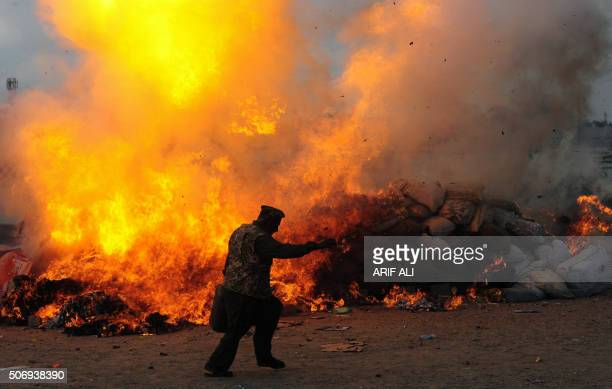 A Pakistani customs official walks past burning drugs and liquor during a ceremony on the occasion of International Customs Day in Lahore on January...