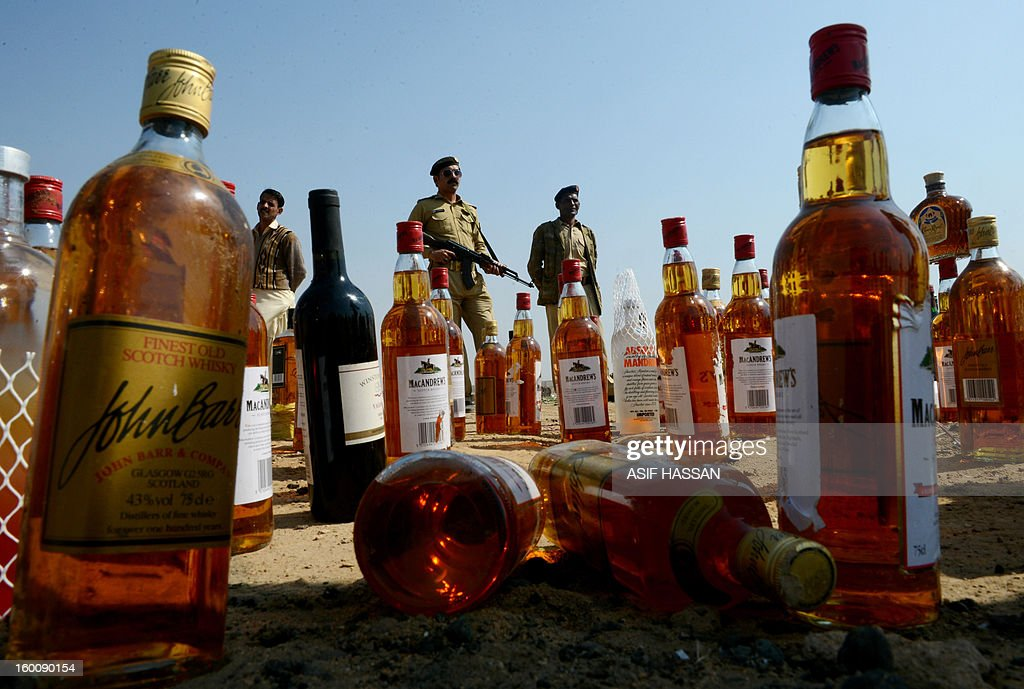 Pakistani Customs officials are pictured behind bottles of alcohol before their destruction in the outskirts of Karachi on January 26, 2013. Pakistan Customs destroyed the contraband as part of International Customs Day. AFP PHOTO/ Asif HASSAN