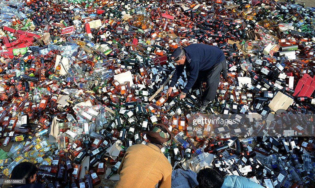 Pakistani customs officials arrange bottles of liquor before destroying them at a ceremony in Lahore on January 26, 2014. Pakistani custom officials destroyed narcotics and other contraband items from different parts of the country to mark the occasion of International Customs Day. AFP PHOTO/Arif ALI
