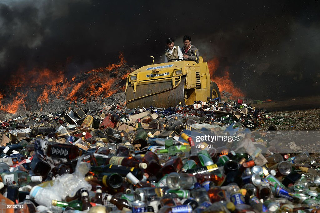 Pakistani customs officials use a steamroller to crush bottles of liquor at a ceremony in Lahore on January 26, 2014. Pakistani custom officials destroyed narcotics and other contraband items from different parts of the country to mark the occasion of International Customs Day. AFP PHOTO/Arif ALI