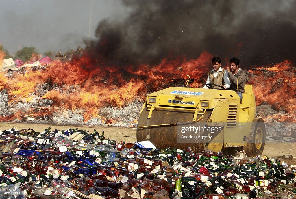 Pakistani customs officials use a steamroller to crush bottles of liquor at a ceremony on the International Customs Day in the outskirts of Lahore, on January 26, 2014.