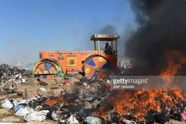 TOPSHOT Pakistani customs officials use a steamroller to crush bottles of liquor on the outskirt of Karachi on January 26 2017 during a ceremony on...