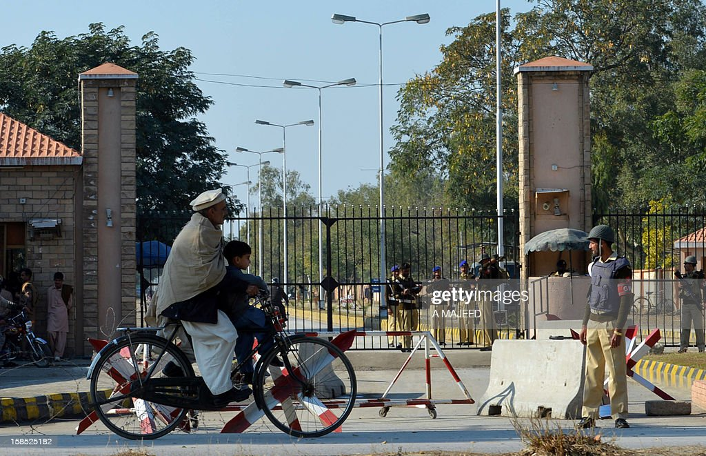 A Pakistani cyclist rides past a check point after a grenade attack near the PAF Engineering Centre in Nowshera on December 18, 2012. According to security forces, unknown attackers riding on two motorbikes hurled two hand grenades near the PAF Engineering Centre that hurt ten people, including five security personnel and five civilians.