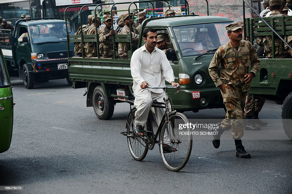 A Pakistani cyclist rides past a convoy of army soldiers near the old city of Lahore on May 10, 2013, one day before some 86 million registered voters will go to the polls to elect lawmakers to the lower house of parliament and four provincial assemblies. Pakistan's general elections will mark the first democratic transition of power in the country's 66-year existence. The Pakistani authorities have deployed tens of thousands of personnel around the country in an effort to safeguard the election process which militant groups have vowed to disrupt. AFP PHOTOS/Roberto SCHMIDT