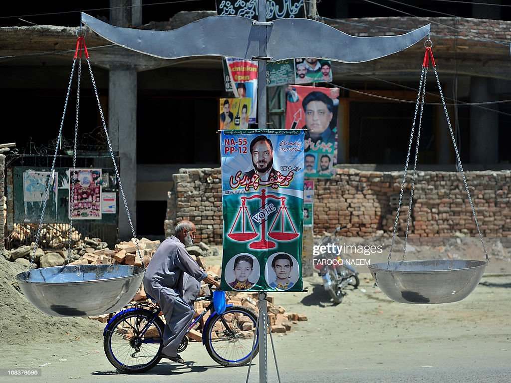 A Pakistani cyclist rides past an installation of a scale, the party symbol of Jamaat-e-Islami, on a street in Rawalpindi on May 9, 2013. The Taliban have sent suicide bombers to mount election-day attacks on Pakistan's historic polls, a militant commander said Thursday, following a bloody campaign which has claimed more than 100 lives. AFP PHOTO/Farooq NAEEM