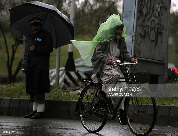 A Pakistani cyclist wears a plastic bag to protect him during a rainy day in Islamabad on March 24 2014 Scattered rain and thunderstorms have been...
