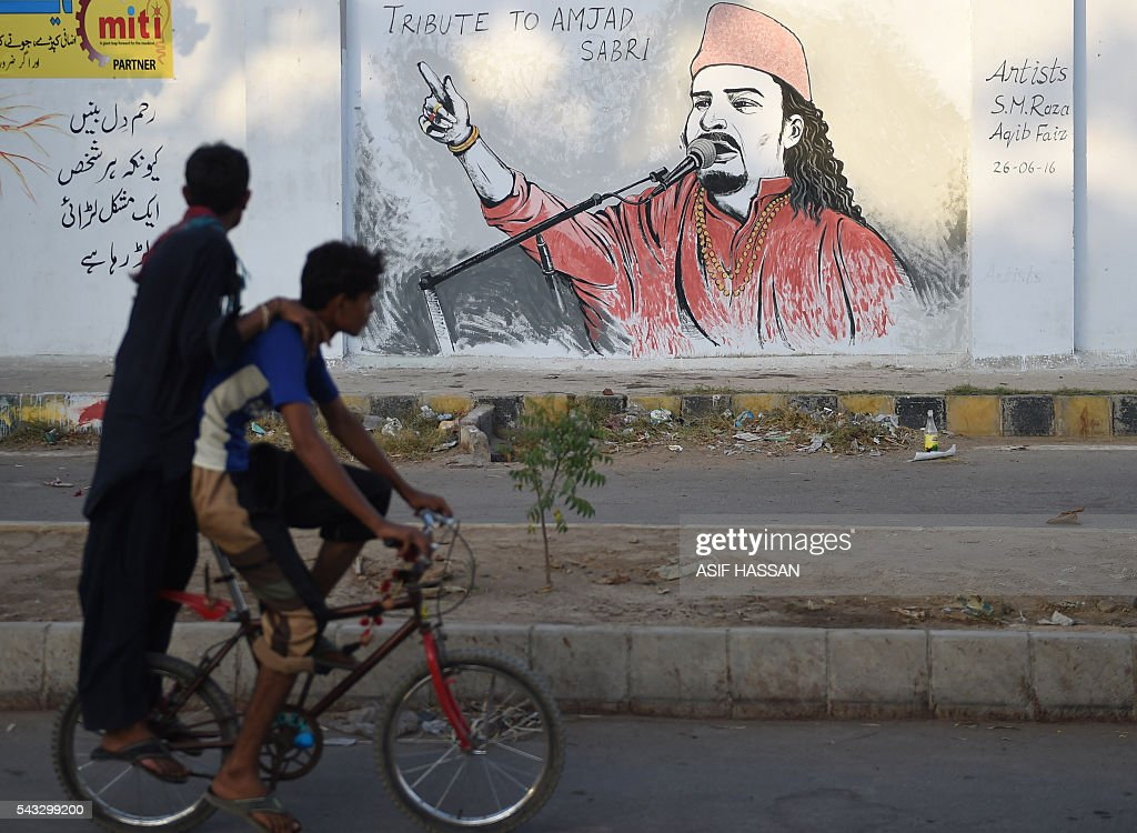 Pakistani cyclists ride past a wall image of late Sufi musician Amjad Sabri alongside a street in Karachi on June 27, 2016. One of Pakistan's best known Sufi musicians Amjad Sabri was shot dead by unknown assailants riding a motorcycle in Karachi on June 22, triggering an outpouring of grief over what police described as an 'act of terror'. / AFP / ASIF