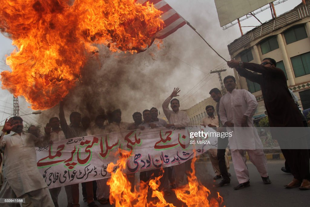 A Pakistani demonstrator holds a burning US flag as others shout slogans during a protest in Multan on May 24, 2016, against a US drone strike in Pakistan's southwestern province Balochistan. Slain Afghan Taliban leader Mullah Akhtar Mansour used a Pakistani passport in a false name to make dozens of foreign trips over a ten-year period, mainly to the United Arab Emirates, officials told AFP. Mansour, who was killed in a US drone strike deep inside Pakistani territory on May 21 along with a driver, was travelling with a passport and ID card bearing the name 'Muhammad Wali'. / AFP / SS