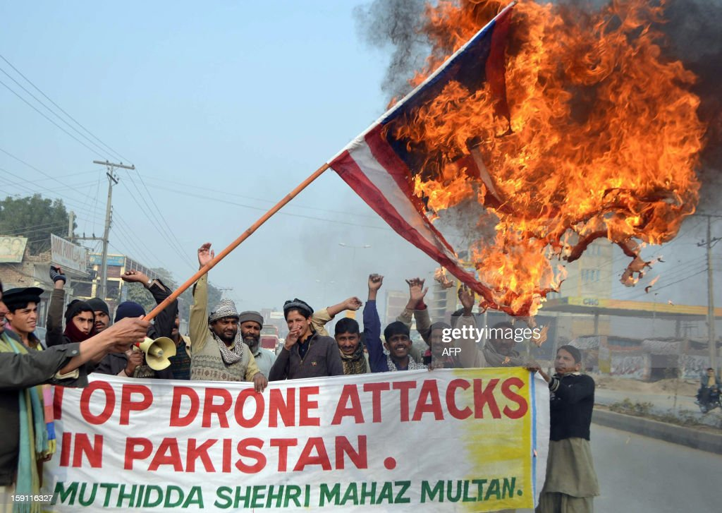 A Pakistani demonstrator holds a burning US flag during a protest in Multan on January 8, 2013, against the drone attacks in Pakistan's tribal areas. At least eight militants were killed and four others wounded on January 8 when US drones fired missiles at militant compounds in a lawless Pakistani tribal area, security officials said. AFP PHOTO/S.S MIRZA