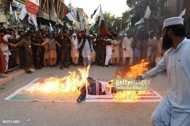 Pakistani demonstrators burn an effigy of US President Donald Trump over an Indian and US flag during a protest in Quetta on August 28 2017 Angry and...