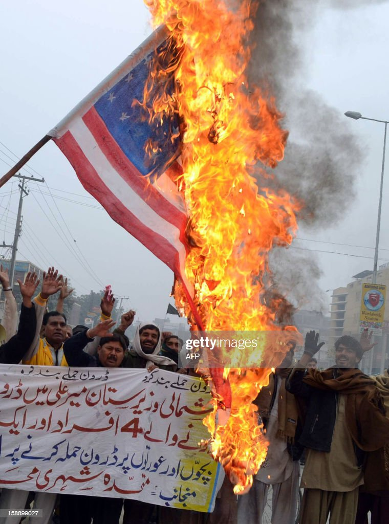 Pakistani demonstrators shout slogans beside a burning US flag during a protest in Multan on January 3, 2013, against the drone attacks in Pakistan's tribal areas. Pakistani warlord Mullah Nazir, who sent men to fight NATO troops in Afghanistan, was killed in a US drone strike in Pakistan along with five loyalists, local security officials said. He was the main militant commander in South Waziristan, part of Pakistan's northwestern tribal belt considered a base for Al-Qaeda, the Taliban and other Islamist militants, and a powerful elder in the Wazir tribe.