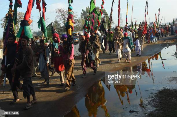 Pakistani devotees carry flags on their journey to the shrine of the Sufi saint Hazrat Daud Bandagi Kirmani for its annual fiveday festival in...