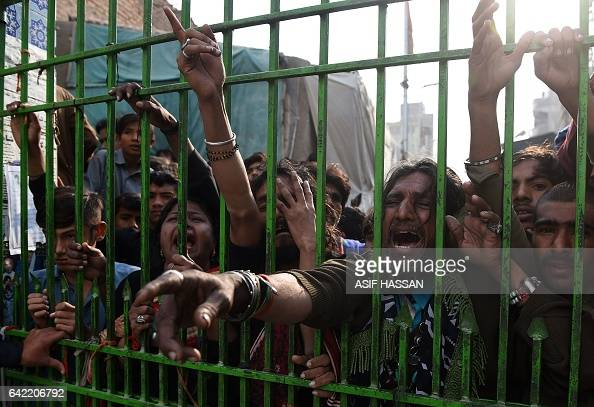 TOPSHOT Pakistani devotees react as they gather outside the closed gate of the shrine of 13th century Muslim Sufi saint Lal Shahbaz Qalandar a day...