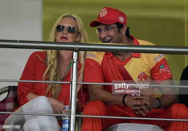 Pakistani director and bowling coach of Islamabad United Wasim Akram watches a match with his wife Shaniera Akram during an exhibition match at...
