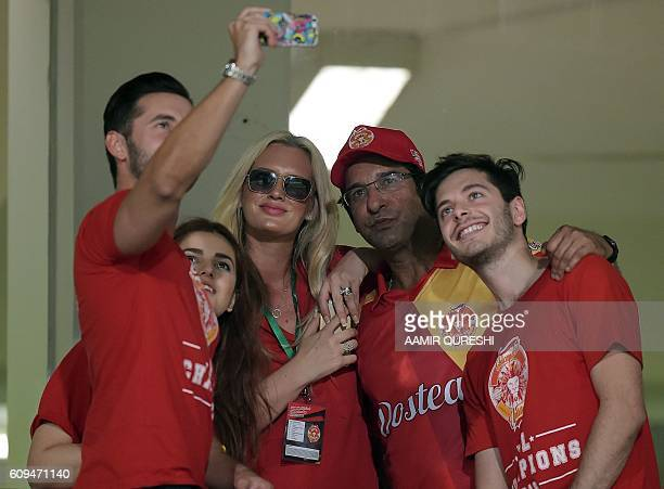 Pakistani director and bowling coach of Islamabad United Wasim Akram and his wife Shaniera Akram take a selfie during an exhibition match at...