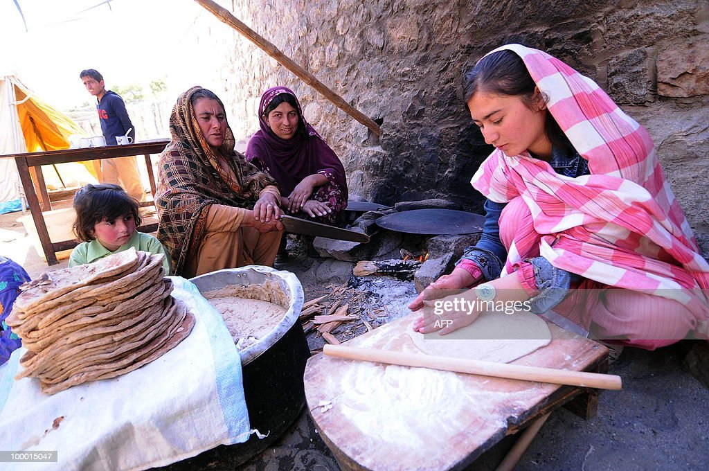 Pakistani displaced village women make bread next to a makeshift camp in the Hunza district of northern Pakistan on May 20, 2010. Flooding from a lake in northern Pakistan risks affecting 40,000 people with residents from up to 34 villages already evacuated to safety, a top disaster management official warned. The artificial lake emerged on January 4 as a result of a massive landslide that killed 20, left about 25,000 people stranded and blocked the Hunza river in a remote Himalayan region about 750 kilometres (450 miles) north of Islamabad.
