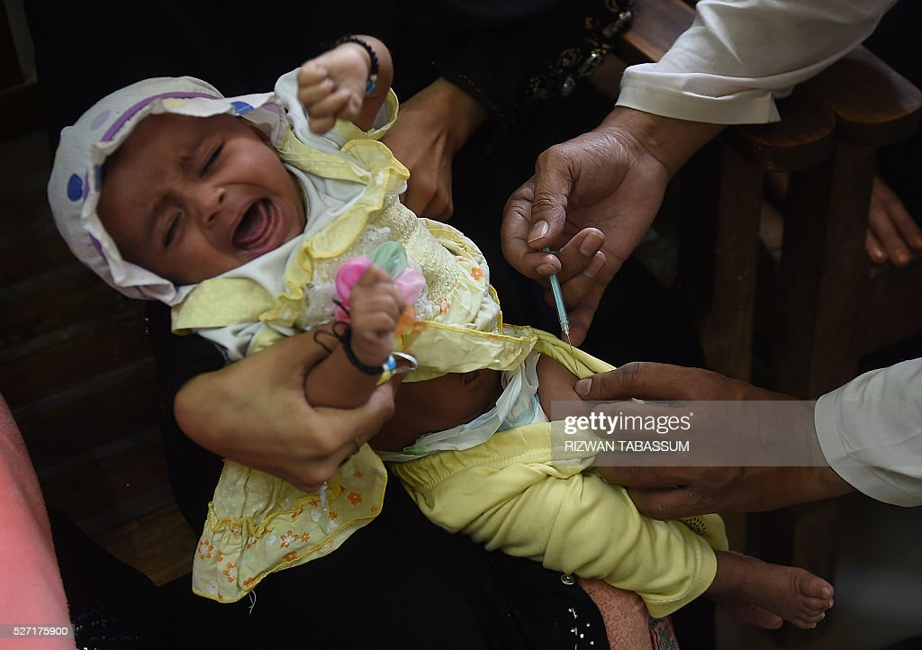 A Pakistani doctor administers the Inactivated Polio Vaccine (IPV) to a child in Karachi on May 2, 2016. Pakistan is one of only three countries in the world where polio remains endemic but years of efforts to stamp it out have been badly hit by reluctance from parents, opposition from militants and attacks on immunisation teams. / AFP / RIZWAN