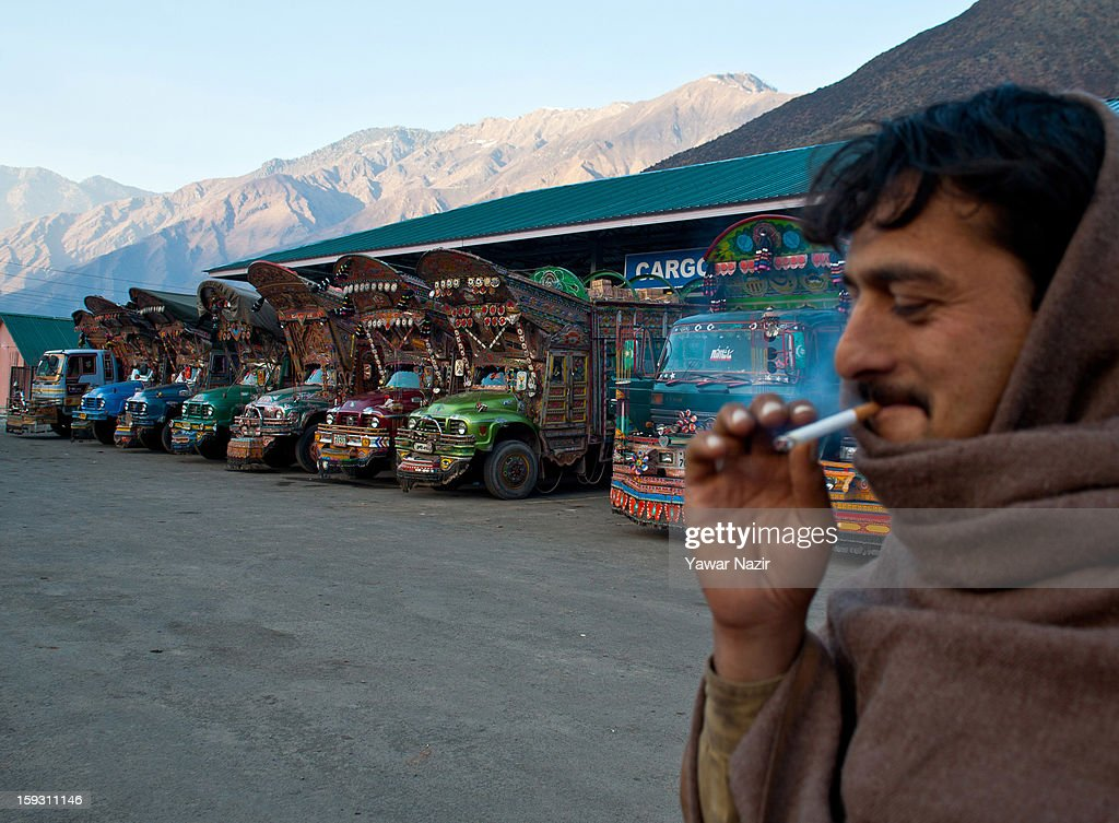 A Pakistani driver smokes a cigarette next to one of his vehicles carrying goods being unloaded at the trade facilitation centre in the border area near Uri on January 11, 2013 in Salamabad, 120 km (75 miles) northwest of Srinagar, the summer capital of Indian Administered Kashshmir, India. People living in the mountainous region along the Line of Control (LOC), a military line that divides Indian-administered Kashmir from the Pakistan-administered Kashmir have continually been at risk due to hostility between the armies of the two rival nations, but trade has been carried out smoothly across the Line of Control in North Kashmir. Two Indian and two Pakistani soldiers have been killed in the last week near the Line of Control dividing Kashmir, with both countries blaming each other for the escalating tension.