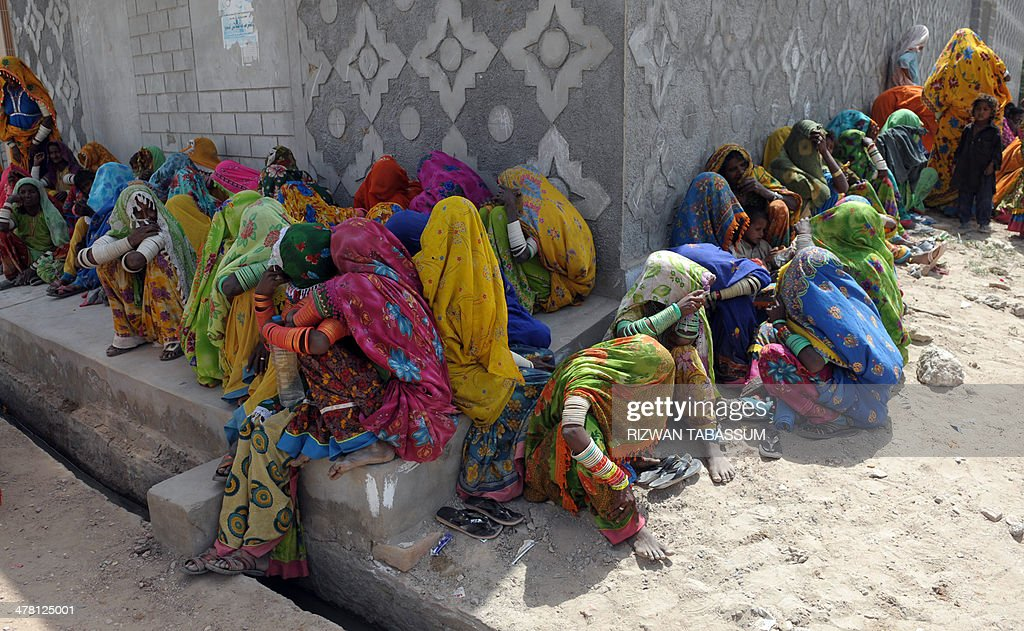 Pakistani drought-affected women wait for relief supplies at a state-run distribution centre in Mithi, the main town in the Tharparkar district in southern Sindh province around 300 kilometres east of Karachi on March 12, 2014. Pakistan govermnment and several private NGOs have set up their relief camps in the drought-hit desert region to provide relief assistance to hundreds of thousands affected families where at least 67 children had died due to malnutrition and other diseases in the area since December. AFP PHOTO/Rizwan TABASSUM
