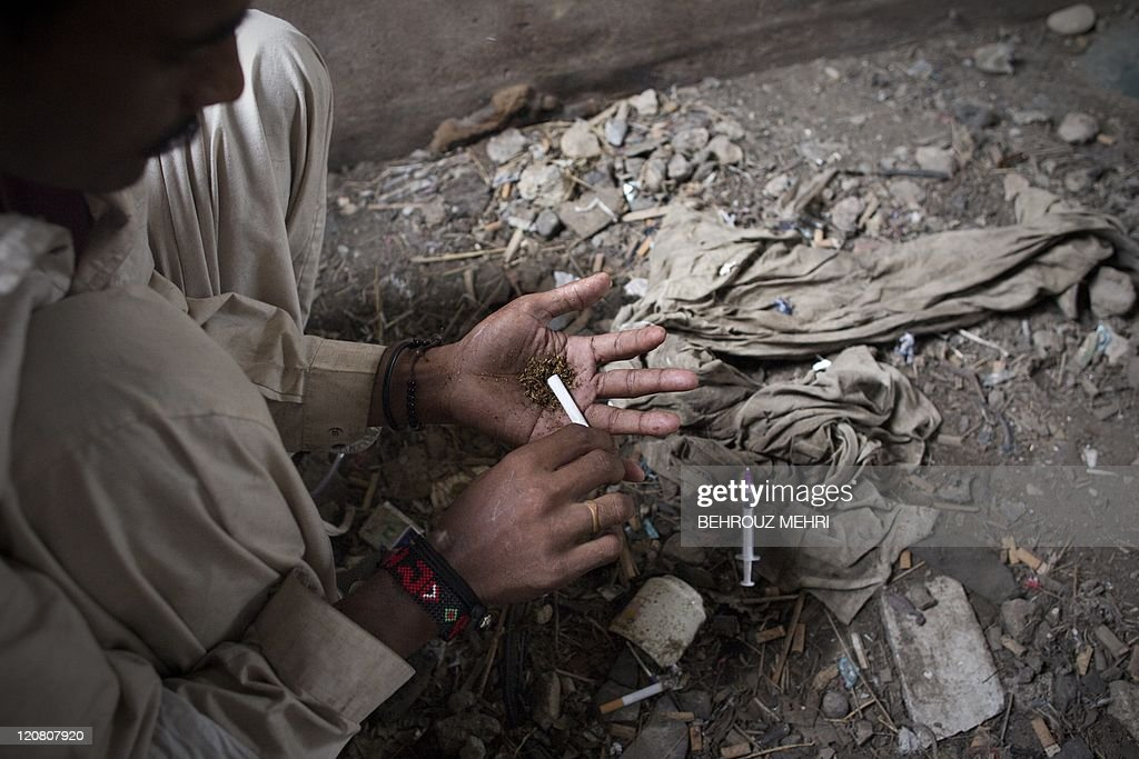 Pakistani drug addict Imran, 29, rolls marijuana after injecting heroin at an abandoned house in 'Kala Pull' (Black Bridge) district of Karachi on July 23, 2011. Pakistan has more than four million drug addicts in its population of 170 million, according to figures compiled by the country's Anti-Narcotics Force (ANF). Pakistan's Central Secretary General of Council of Herbal Physician Hakeem Qazi M.A. Khalid said that around 50 billion rupees were wasted in drug addiction every year in the country and 130,000 people took intoxicants through injections while 80 percent addicts used the same syringes which were also cause of fatal diseases. Most of the heroin is smuggled from neighbouring Afghanistan through Pakistan's northwestern province of Khyber Pakhtunkhwa. AFP PHOTO/BEHROUZ MEHRI