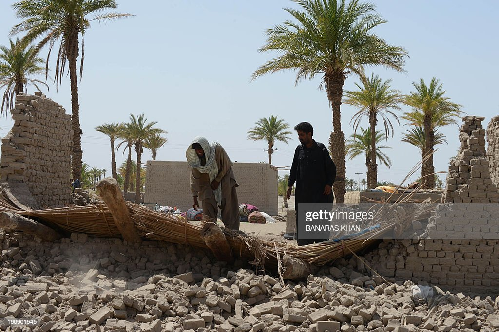 A Pakistani earthquake survivor and a frontier constabulary soldier examine a collapsed mud house in the quake hit Mashkail area of southwestern Baluchistan province on April 18, 2013. More than 12,000 Pakistanis living in a remote, impoverished southwestern desert region near the Iranian border have been affected by this week's huge earthquake, a relief official said. AFP PHOTO/ BANARAS KHAN