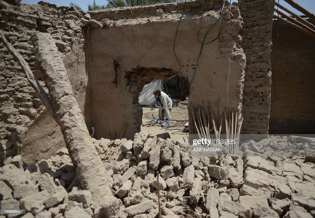 A Pakistani earthquake survivor holds his child as he tries to carry a bicycle in front of his collapsed mud house in the quake hit Mashkail area of southwestern Baluchistan province on April 18, 2013. More than 12,000 Pakistanis living in a remote, impoverished southwestern desert region near the Iranian border have been affected by this week's huge earthquake, a relief official said.
