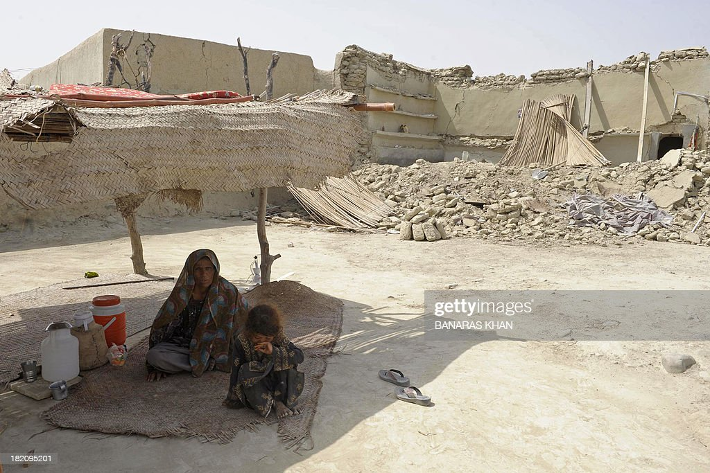 A Pakistani earthquake survivor sits under a makeshift shelter in the devastated district of Awaran on September 25, 2013. A powerful 6.8-magnitude earthquake hit southwest Pakistan, in a region already devastated by a tremor which left more than 300 people dead and 100,000 homeless less than a week ago. AFP PHOTO/ Banaras KHAN