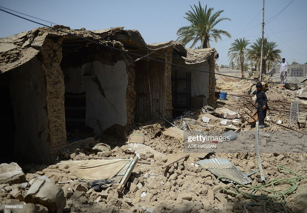 A Pakistani earthquake survivor walks past collapsed mud houses in the quake hit Mashkail area of southwestern Baluchistan province on April 18, 2013. More than 12,000 Pakistanis living in a remote, impoverished southwestern desert region near the Iranian border have been affected by this week's huge earthquake, a relief official said. AFP PHOTO/ ASIF HASSAN