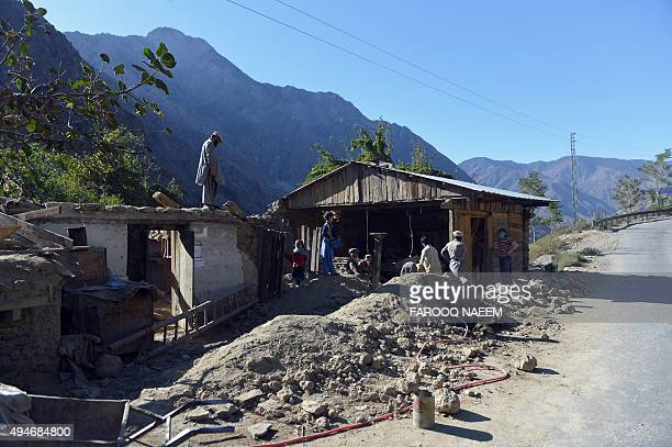 Pakistani earthquake survivors rebuild their house in Kesu village some 15 km from Chitral on October 28 2015 Digging through the rubble of an...