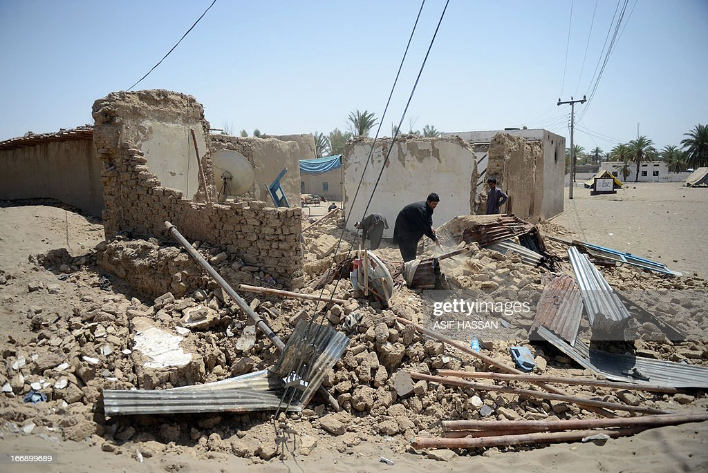Pakistani earthquake survivors remove debris of their collapsed mud houses in the quake hit Mashkail area of southwestern Baluchistan province on April 18, 2013. More than 12,000 Pakistanis living in a remote, impoverished southwestern desert region near the Iranian border have been affected by this week's huge earthquake, a relief official said. AFP PHOTO/ ASIF HASSAN