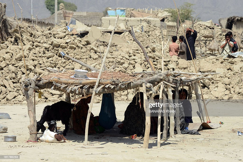 Pakistani earthquake survivors sit under a makeshift shelter near their collapsed mud houses in the earthquake-devastated district of Awaran on September 25, 2013. The death toll from a major earthquake that hit southwestern Pakistan rose to 328 on September 25, officials said, with more fatalities feared as rescue teams reach the remote affected area. AFP PHOTO/Banaras KHAN