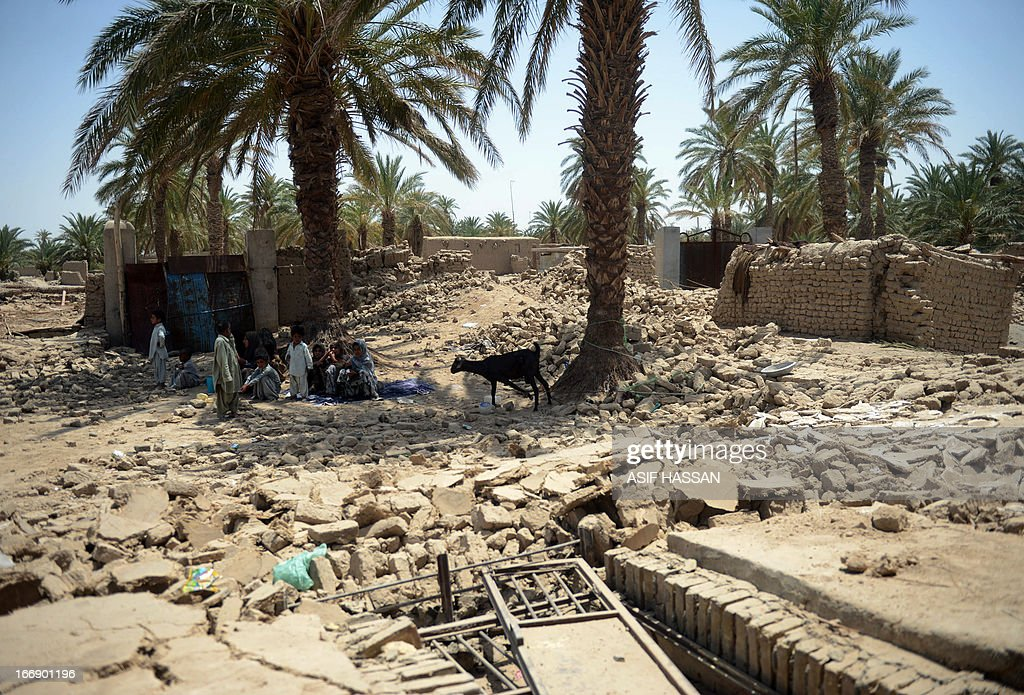 Pakistani earthquake survivors sit under a tree next to collapsed mud houses in the quake hit Mashkail area of southwestern Baluchistan province on April 18, 2013. More than 12,000 Pakistanis living in a remote, impoverished southwestern desert region near the Iranian border have been affected by this week's huge earthquake, a relief official said.