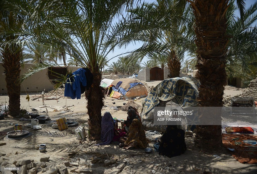Pakistani earthquake survivors sit under trees near collapsed mud houses in the quake hit Mashkail area of southwestern Baluchistan province on April 18, 2013. More than 12,000 Pakistanis living in a remote, impoverished southwestern desert region near the Iranian border have been affected by this week's huge earthquake, a relief official said.