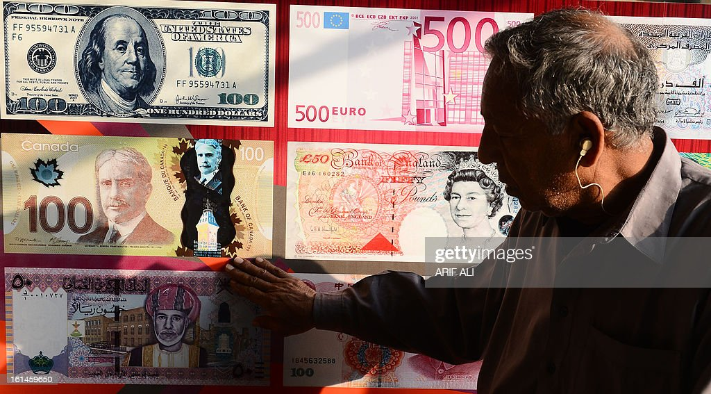 A Pakistani elderly man looks at a currency exchange shop in Lahore on February 11, 2013. The Pakistani rupee on sank to an all-time low against the US dollar over forex reserve fears as the country repayed USD 146 million to the International Monetary Fund. AFP PHOTO/ Arif ALI