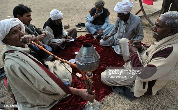 A Pakistani elderly man smokes a Huqa as others play cards in Islamabad on February 1 2010 Longer lifespans falling fertility rates and growing ranks...