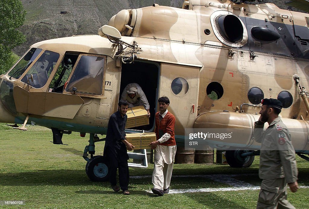Pakistani election officials unload electoral material from an army helicopter for the upcoming parliamentary elections, in northwestern Chitral valley on May 3, 2013. A candidate running for parliament in next week's historic Pakistani election was shot dead on Friday along with his three-year-old son after praying in a mosque in Karachi, police said.