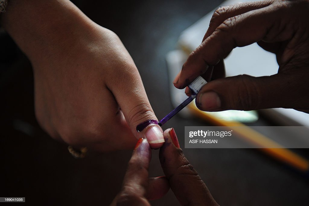 A Pakistani election presiding officer marks a voter's thumb with indelible ink during the re-poll of voters in the constituency known as NA-250 in Karachi on May 19, 2013. Hundreds of people queued up at 43 polling stations in a constituency of Pakistan's port city of Karachi on Sunday where a re-vote had been ordered over allegations of ballot stuffing. AFP PHOTO/Asif HASSAN
